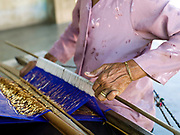 An elderly Hindu Cham woman weaves a priest's turban with cotton and silk thread on a back-strap loom at home in My Nghiep village, Ninh Thuan province, Central Vietnam. The Cham people are remnants of the Kingdom of Champa (7th to 18th centuries) and are recognised by the government as one of Vietnam's 54 ethnic groups.