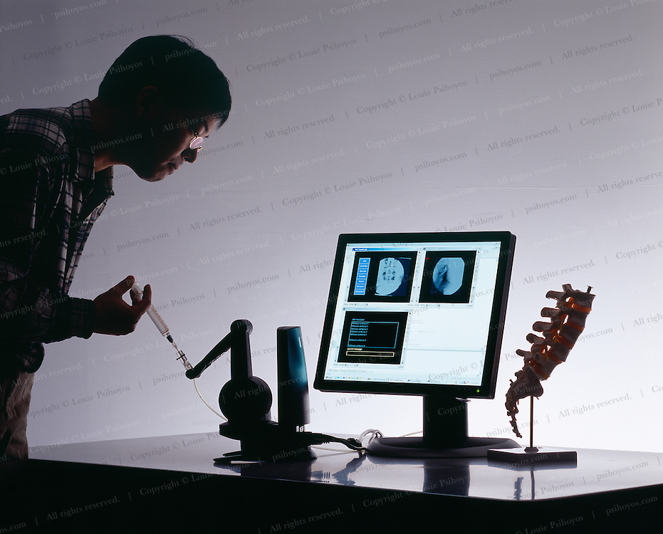 A reseacher at the Touch Lab uses a device to simulate the injection of a fluid in the spinal cord.  The device is outfitted with actuators and braks and gives sensitive feedback to the doctor to what the pressure feels like as the syringe enters the dagerous area around the spinal column.