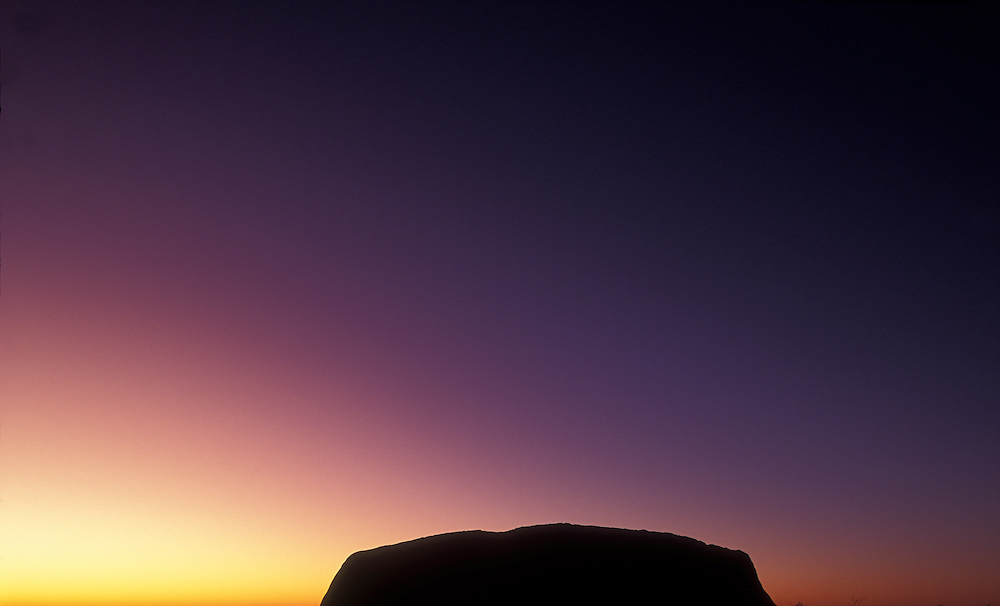 Australia, Northern Territory, Morning twilight silhouettes the 348 meter high Ayers Rock in Uluru National Park