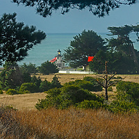 Pines and Cypress trees frame Point Cabrillo Light Station on the Pacific coast of California in Mendocino County.