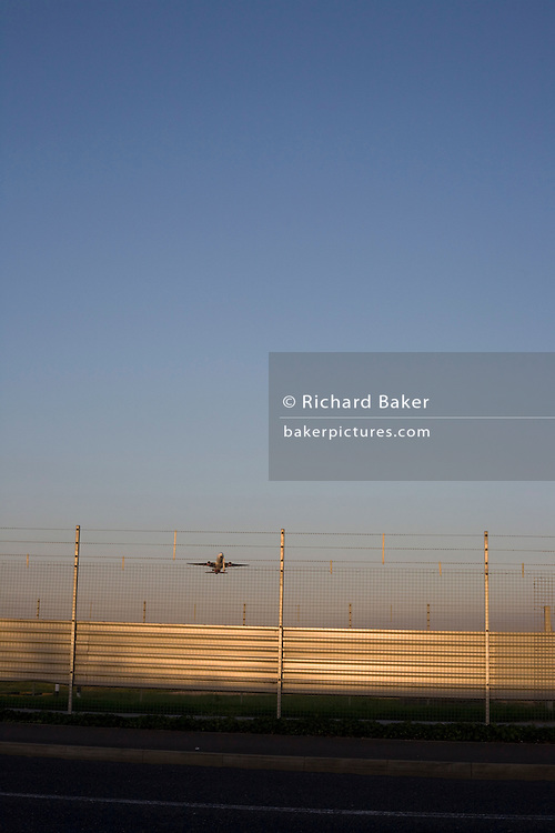 An airliner crosses the security perimeter fence at Heathrow Airport on its way to an international destination.