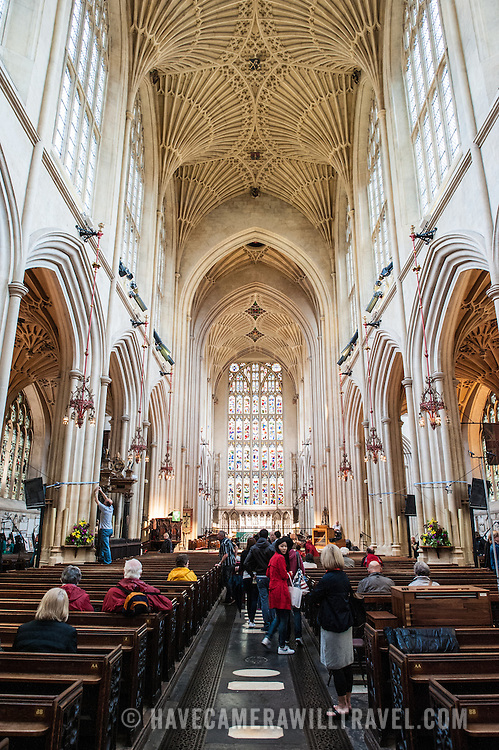 People sit in the pews in the nave of Bath Abbey. .Bath Abbey (formally the Abbey Church of Saint Peter and Saint Paul) is an Anglican cathedral in Bath, Somerset, England. It was founded in the 7th century and rebuilt in the 12th and 16th centuries.