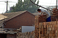 China, Beijing, Chaoyang, San Jian Fang, 2008. Taking care with his work, a bricklayer helping to rebuild Chaoyang street businesses puts the finishing touches on a wall.