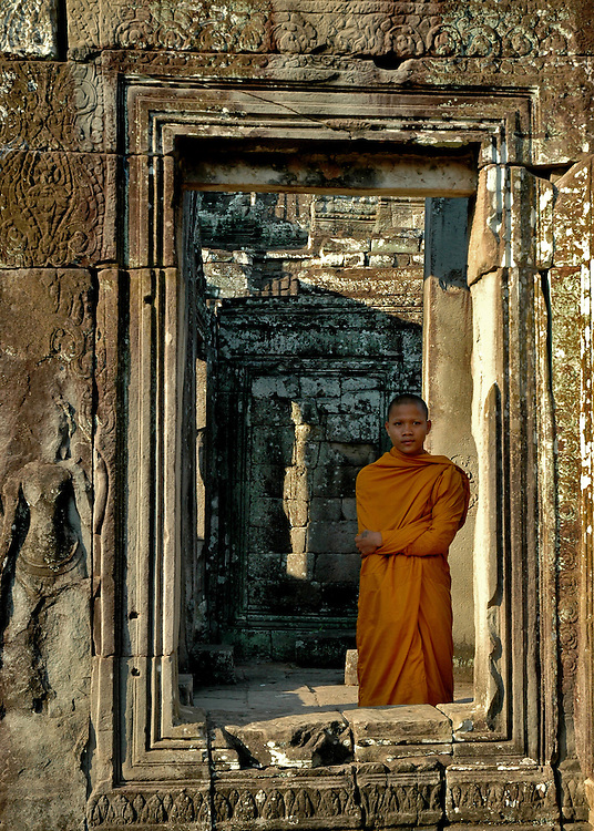 This image of a Cambodian Buddhist Monk was shot at the Bayon temple in Angkor Thom city.<br /> <br /> The Bayon is the second most well known temple after Angkor Wat in the Angkor complex located at the center of Angkor Thom city.  The ruins of Angkor, a UNESCO World Heritage Site with temples numbering over one thousand, are hidden amongst forests and farmland to the north of the Tonle Sap Lake (Great Lake) and south of the Kulen Hills outside the modern city of Siem Reap, Cambodia.  Angkor served as the seat of the Khmer empire and flourished from approximately the 9th century to the 13th century. <br /> <br /> Built in the late 12th or early 13th century as the official state temple of King Jayavarman VII,  the Bayon temple is comprised of <br /> 54 towers with the smiling face of Avalokiteshvara.<br /> <br /> These Buddhist Saints or bodhisattva embody the compassion of all Buddhas and are a beautiful and powerful sight to behold. Exploring the Bayon was an amazing experience.