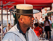 """Gondolier. Gondolas are traditional, flat-bottomed rowing boats which ferry people through Venetian canals. From a peak of 10,000 gondolas 200 years ago, just 500 gondolas now serve the city. The banana-shaped modern gondola was developed in the 1800s. The left side of the gondola is made longer than the right side to resist leftwards drift at the forward stroke. The gondolier stands on the stern facing the bow and rows just on the right side, with a forward stroke and compensating backward stroke. The oar or rèmo is held in an oar lock, or fórcola, shaped for several rowing positions. The decorative fèrro (meaning iron) ornament on the front can be made of brass, stainless steel, or aluminum, as counterweight for the gondolier standing near the stern. The six horizontal lines and curved top of the ferro represent Venice's six sestieri (districts) and the Doge's cap. Painting gondolas black originated as a sumptuary law eliminating ostentatious competition between nobles. Until the early 1900s, many gondolas had a small cabin (felze) with windows which could be closed with louvered shutters--the original """"venetian blinds."""" The romantic """"City of Canals"""" stretches across 117 small islands in the marshy Venetian Lagoon along the Adriatic Sea in northeast Italy, Europe. Venice and the Venetian Lagoons are honored on UNESCO's World Heritage List. For licensing options, please inquire."""