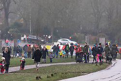 © Licensed to London News Pictures. 01/01/2021. London, UK. Members of the public enjoy a New Year's Day walk despite the cold, rain and snow flurries in a busy Richmond Park, South West London today as temperatures dropped to -7c this morning in parts of the South East. On Wednesday the Oxford vaccine was approved for use, with the government securing over 100 million doses with an expected full rollout of vaccinations from Monday, January 4th 2021 as the coronavirus pandemic continues into the new year. UK. Photo credit: Alex Lentati/LNP