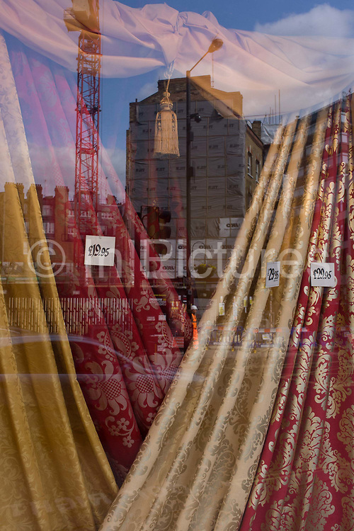 Display of curtains (drapes) in a central London street shop window. Arranged in a neat display across the width of the window are the fabrics of someone's future home, the tastes being traditional and slightly retrospective with the quality reflected in the low prices, seen on labels alongside the material. A building is under construction in the background, across the road with a crane seemingly lifting the tassel that dangles from the store's ceiling.