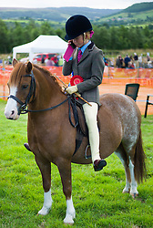 © Licensed to London News Pictures.29/08/15<br /> Bilsdale, UK. <br /> <br /> A young rider speaks to a friend on her phone after winning her class during competition at the 105th Bilsdale Country Show in North Yorkshire.<br /> <br /> Photo credit : Ian Forsyth/LNP