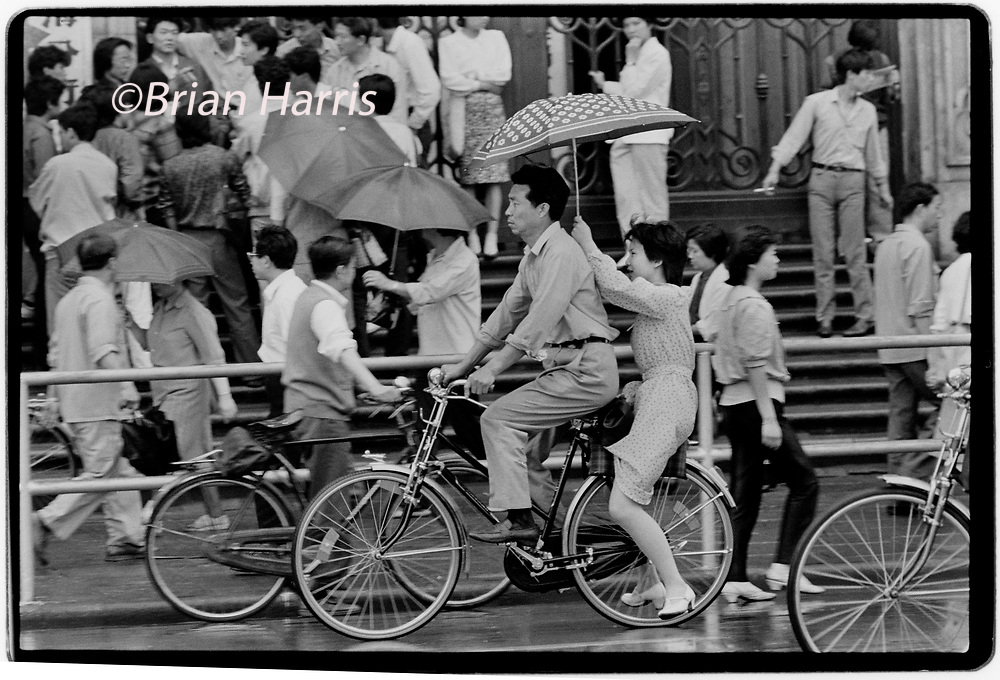 China Shanghai a few days after the massacre in Tiananmen Square in June 1989. Scans made in 2018<br /> Men and wonen on bicycles in Shanghai in the rain.
