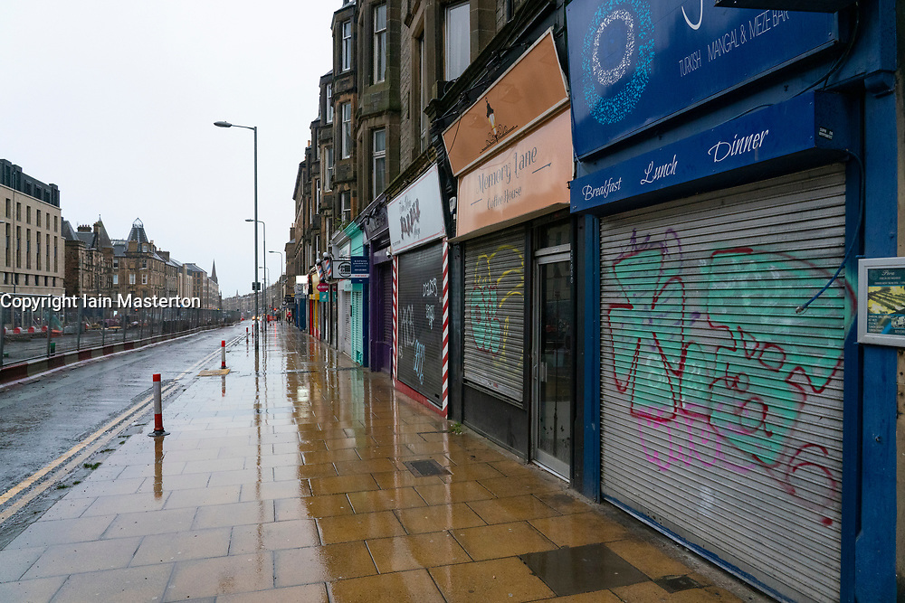Edinburgh, Scotland, UK. 26 December 2020. Scenes from Edinburgh City Centre on a wet and windy Boxing Day during storm Bella. Today is first day that Scotland is under level 4 lockdown and all non essential shops and businesses are closed. As a result the streets are almost deserted with very few people venturing outside. Pic; Leith Walk looks desolate with most businesses shut.  Iain Masterton/Alamy Live News