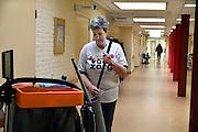 Nederland, Arnhem, 18-03-2014 Bij zorginstelling Vreedenhoff werd dinsdagmiddag een protestactie gehouden. Werknemers onderbreken het werk voor 1 minuut en maken een foto, groepsfoto die ze opsturen aan de vakbond Abva Kabo, FNV. Een schoonmaakster weer het werk na de actie.Foto: Flip Franssen