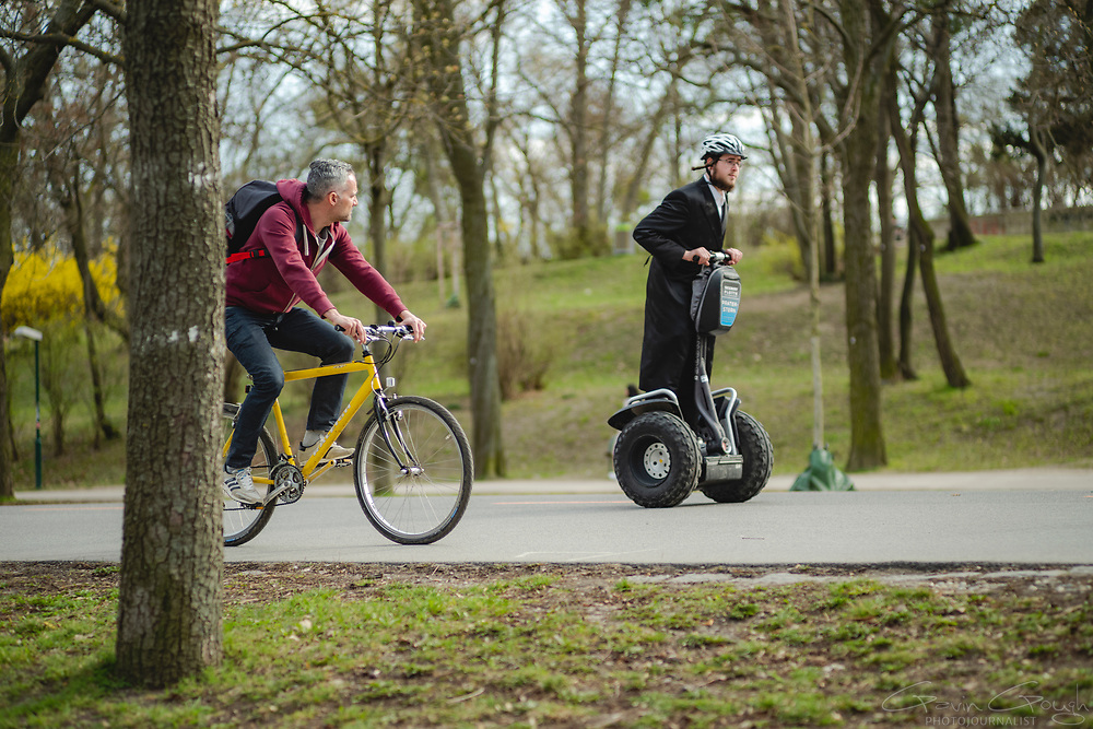 A cyclist and a Jewish man riding a Segway in the park, Prater Park, Vienna, Austria