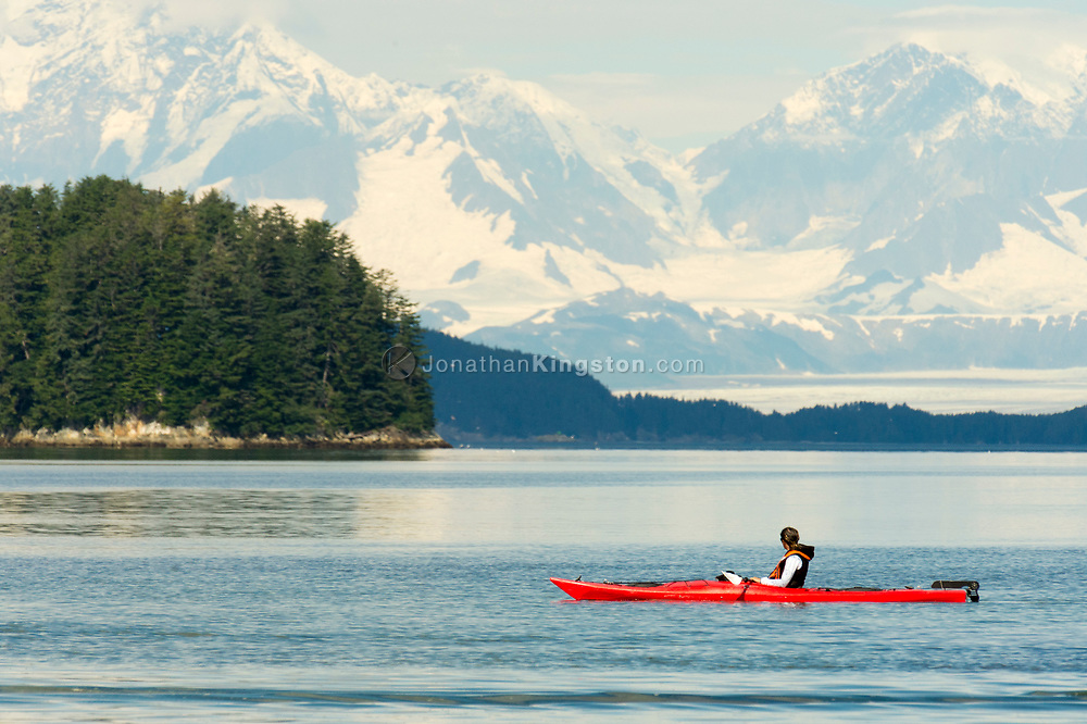 A woman in a red kayak looks at massive snow covered mountains near Port Althorp in south east Alaska.