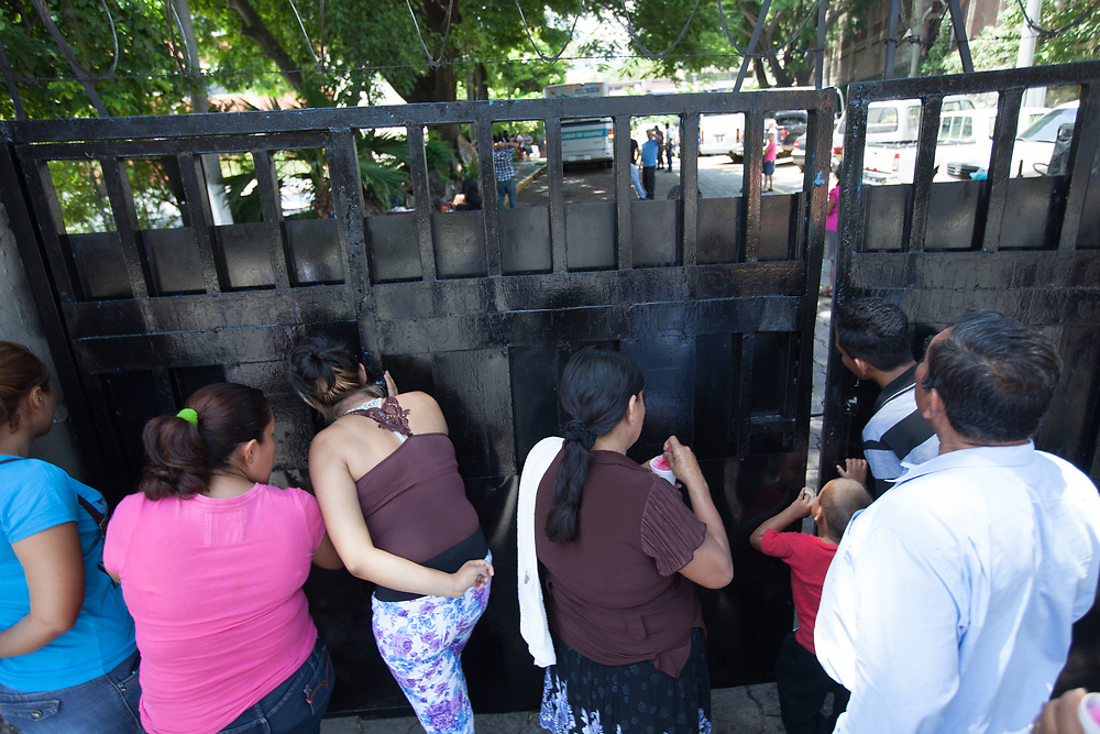 Family members peer through gaps in the gate to see if their children have arrived at a centre for repatriated migrants in El Salvador. El Salvador receives several buses and planes full of deported migrants every day. Child migrant deportations from the US and Mexico to Honduras, Guatemala and El Salvador are at a crisis level, where government provision to deal with the wave of repatriations is inadequate. In San Salvador, hundreds of children are repatriated daily.
