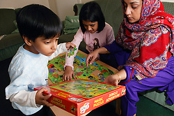 Single parent helping her young children do a jigsaw puzzle,