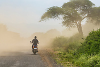 Man riding motorcycle down a dusty road, Southern Nations Nationalities and People's Region, Ethiopia.