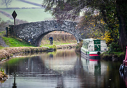 © Licensed to London News Pictures. 17/11/2020. Brecon, UK. A cyclist rides along the banks of the Monmouthshire and Brecon Canal in Brecon, Wales on a typical Autumn day as blustery and wet weather grips the UK and is forecast to remain throughout the week. Photo credit: Robert Melen/LNP