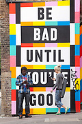 A man and a woman check their mobile telephones by a humorous sign, Shoreditch, London, UK<br /> Shoreditch, an area that was dominated by light industry is now home to creatives and the streets are decorated with a good deal of graffiti - much by established street artists