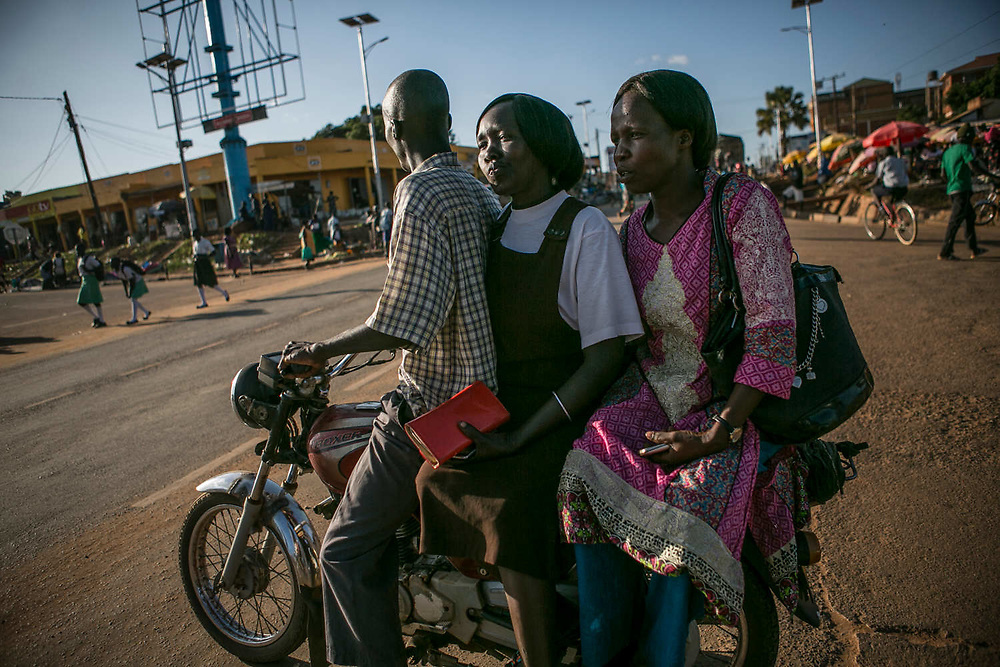 Aciro Scolvia, center, about 39, and Acheng irine, about 34, right, former roommates of St. Mary's school in Gulu, ride on a motorbike taxi together in Gulu town. They were both abducted by LRA forces in the middle of the night when they were about 13 years old and were assigned to commanders six months later. Scolvia became the third wife and Irine became the 7th wife of different commanders and gave birth to children from each man. After they escaped separately, they reunited at a vocational center called GYDA and received job training as a building painter.