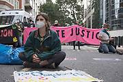 """Protester sits in front of the Home Office at the """"Climate Justice is Migrant Justice"""" protest, outside Home Office, Marsham Street in central London on Friday, Sept 4, 2020. (VXP Photo/ Gio Strondl)"""