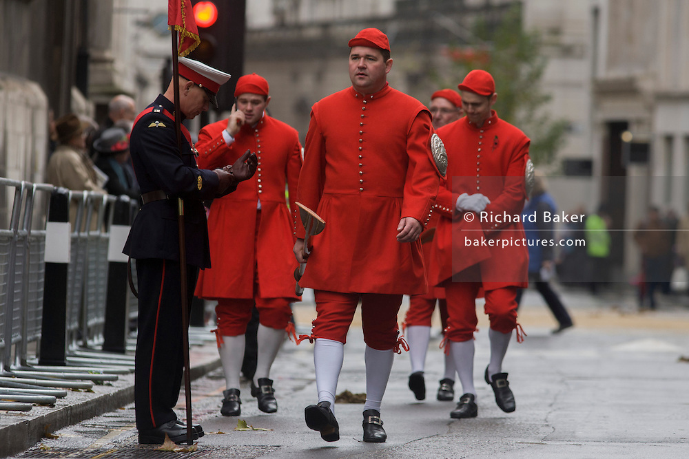 Members of Doggett's Coat and Badge walk towards the Guldhall before the Lord Mayor's Show in the City of London. Alderman and Rt Hon The Lord Mayor of London, Roger Gifford, a merchant banker with Swedish bank SEB is the 685th in the City of London's ancient history. The new Mayor's procession consists of a 3-mile, 150-float parade of commercial and military organisations going back to medieval times. This is the oldest and longest civic procession in the world that has survived the Plague and the Blitz, today one of the best-loved pageants. Henry Fitz-Ailwyn was the first Lord Mayor (1189-1212) and ever since, eminent city fathers (and one woman) have taken the role of the sovereign's representative in the City - London's ancient, self-governing financial district. The role ensured the King had an ally within the prosperous enclave. .