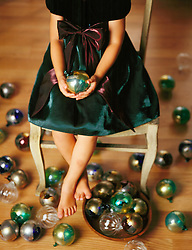 Little girl party dress sitting in chair surrounded by Christmas ornaments