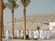 Men gather in front of the Louvre Abu Dhabi, an art and civilization museum. Architect is Jean Nouvel.