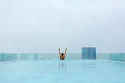 Rear View of Woman in Roof Swimming Pool with Arms raised. Bangkok, Thailand