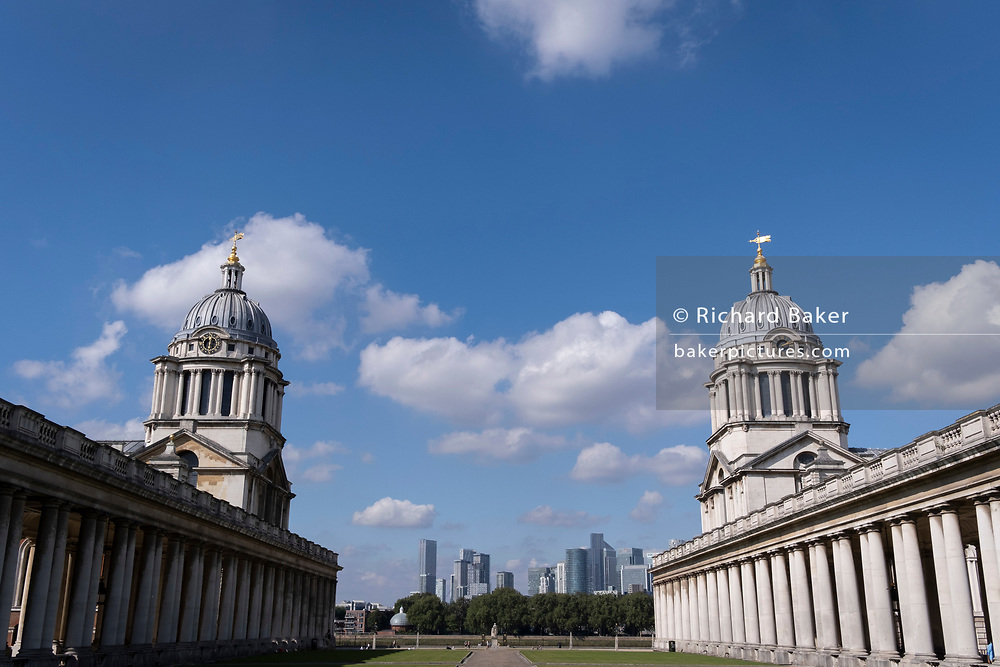With modern corporate high-rise offices in the distance across the Thames, the twin domes of the Royal Naval Hospiral at Greenwich are seen, on 16th September 2021, in London, England. Greenwich Hospital was a permanent home for retired sailors of the Royal Navy, which operated from 1692 to 1869. It was later used by the Royal Naval College, Greenwich and the University of Greenwich, and are now known as the Old Royal Naval College.