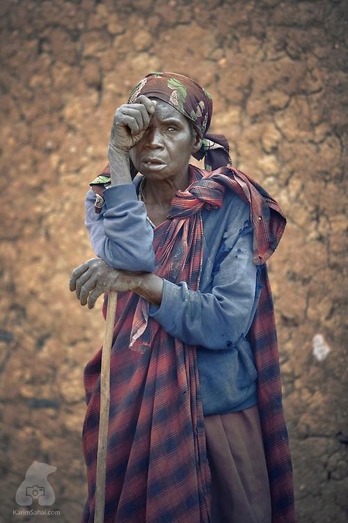 Woman resting on a walking stick, Kagano, Rwanda