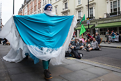 Environmental activists from Extinction Rebellion dressed as the sea take part in the first day of Impossible Rebellion protests in the Covent Garden area on 23rd August 2021 in London, United Kingdom. Extinction Rebellion are calling on the UK government to cease all new fossil fuel investment with immediate effect. (photo by Mark Kerrison/In Pictures via Getty Images)