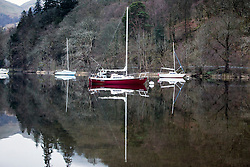 © Licensed to London News Pictures. 14/04/2016. Ullswater UK. Boats are reflected in the calm water of Ullswater lake in Cumbria this morning. Weather forecasters predict scattered showers in the south & drier in the north.  Photo credit: Andrew McCaren/LNP