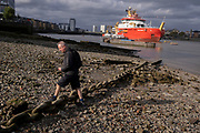 A Londoner steps over an old shipbuilding chain on the Thames foreshore, where the British Antarctic Survey's new polar research ship, the RRS Sir David Attenborough is moored on the Thames at the Prime Meridian, Greenwich, during its short stay on show to the public, during the COP26 Climate Change conference in Glasgow, on 28th October 2021, in London, England. The  £200m Attenborough is a Polar Class 4 icebreaker with state of the art  research equipment, a helipad, cranes, onboard laboratories, and other ocean-survey and sampling equipment.
