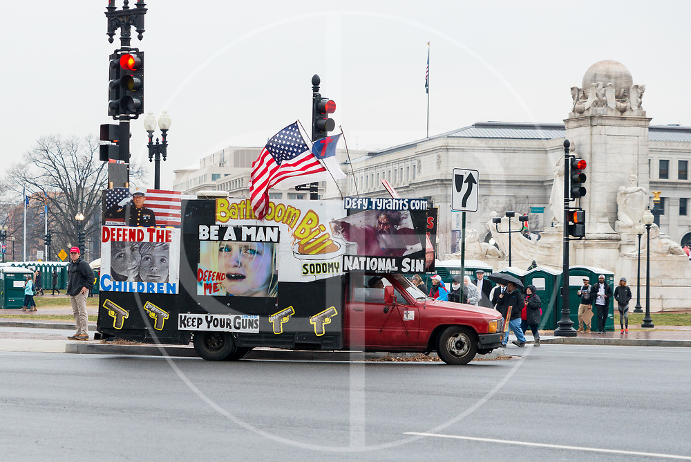 Washington DC, United States - A truck with an array of politically-motivated signs drives through the streets of Washington D.C. on Inauguration Day, 2017.