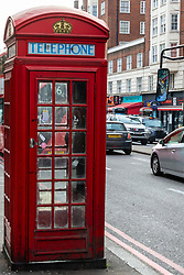 A traditional British phonebook is seen with its more modern counterparts in the distance across the road as modern public telephones carrying illuminated advertising add to the clutter of signs, lampposts, sandwich boards, bus shelters and street furniture on Edgeware Road in London. LONDON, February 12 2019.
