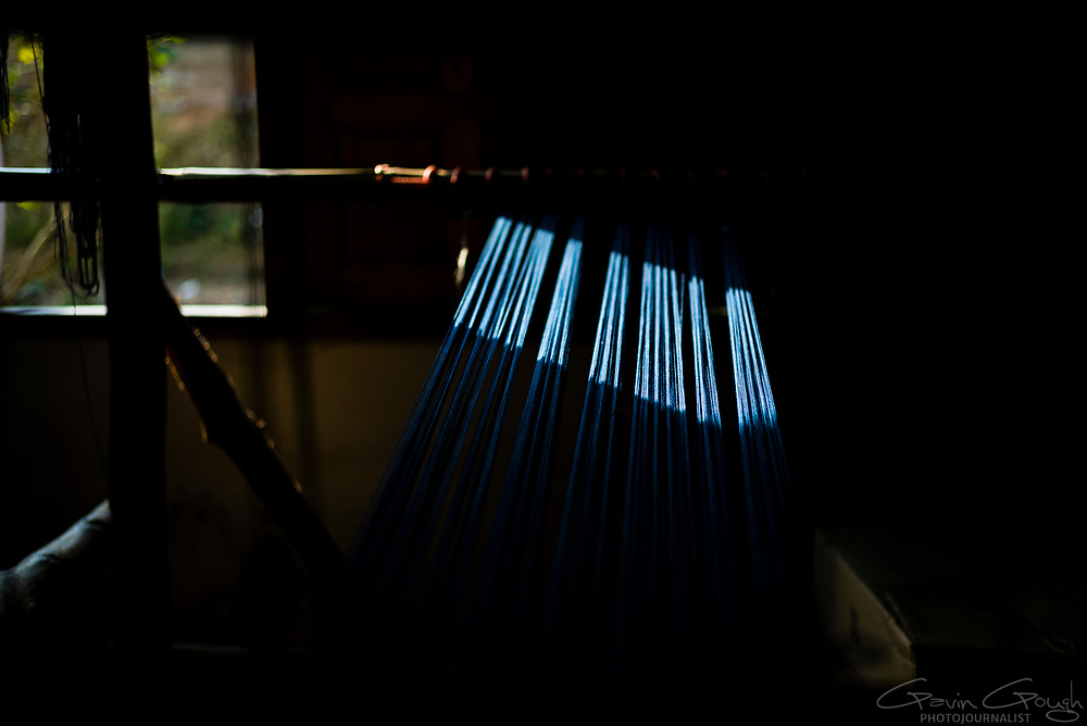 Sunlight shining upon woollen yarn dyed with indigo and stretched upon a wooden loom, Indigo Dyeing Factory, Sakhon Nokhon, Thailand