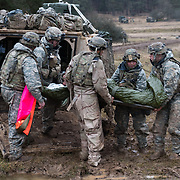 Soldiers from 1st Battalion, 8th Cavalry, 1st Cavalry Division unload patients from an armored troops carrier during Combined Resolve XIII, Feb. 1, 2020, at Hohenfels Training Area.  (U.S. Army photo by Sgt. 1st Class Garrick W. Morgenweck)