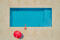Aerial view of young girl in sunhat sitting by swimming pool and red parasol, Sumartin, Brac island, Croatia.