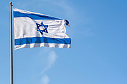 Blue and white Israeli flag blows in the wind with a blue sky background