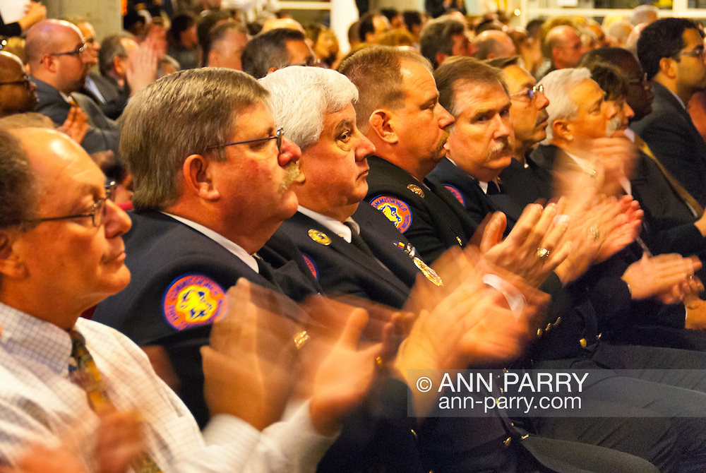Nassau County Executive Edward Mangano gives State of the County Address, on Wednesday night, March 14, 2012, at Cradle of Aviation museum, Garden City, New York, USA. Shown clapping their hands is audience, including several Nassau County Fire Department Commissioners: 2nd from right: Robert Cribbin, 4th Battalion Chairman, 3rd from right: C. Richard Gardner, 1st Battalion; 4th from right: Walter Weltner, 3rd Battalion Chairman, Fire Commission; 6th from right:Joseph Stallone, 2nd Battalion; 7th from right: Ralph Esposito, 7th Battalion;