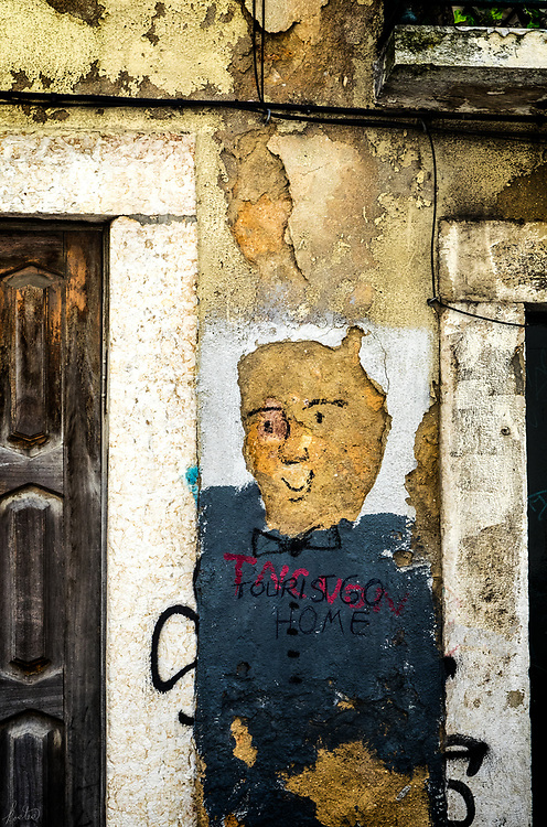 Graffiti on a crumbling wall in Lisbon with tourista home written on it.