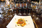 Slices of roast duck's breast placed on top of a ravioli with angle hair thin French fried potatoes on a white plate with a branch of thyme. And eight glasses of a vertical tasting of Angel A Mendoza Malbec Cabernet Sauvignon Pura Sangre Domaine St Diego Lunlunta Maipu Mendoza The O'Farrell Restaurant, Acassuso, Buenos Aires Argentina, South America
