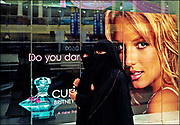 Two Arab women in traditional black veils, head coverings, and long smock-like cloaks--drawn over usually attractive and colorful dresses to preserve modesty in public--walk past a picture of pop singer Britney Spears in the posh City Centre Shopping Center in Dubai.  The picture of Ms. Spears was posted in the window of a perfume store to promote a line of fragrances that use Ms. Spear's name.  © Steve Raymer 2005 / Getty Images /ALL RIGHTS RESERVED