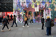 People passing a large scale floral window display for a clothing retailer on Oxford Street on 21st January 2020 in London, England, United Kingdom. Oxford Street is a major road in the West End of London. It is Europes busiest shopping street, with around half a million daily visitors, and has approximately 300 shops.