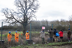 Harefield, UK. 18 February, 2020. Environmental activists from Save the Colne Valley, Stop HS2 and Extinction Rebellion monitor HS2 workers, accompanied by security guards, as they survey a large tree on a site in the Colne Valley earmarked for the HS2 high-speed rail link.