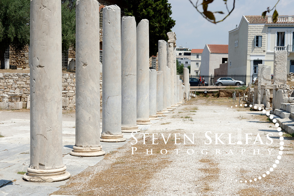 Athens. Greece. Part view of the elegant Ionic peristyle that enclosed the central open space of the ancient Roman Agora in Athens. The marble columns were unfluted and the courtyard was paved with marble during the time of Hadrian. Dating from the 1st century BC, the Roman Agora is about 100 metres to the east of the Ancient Agora and is complex consisting of a large rectangular open courtyard surrounded by stoas, shops and storerooms.