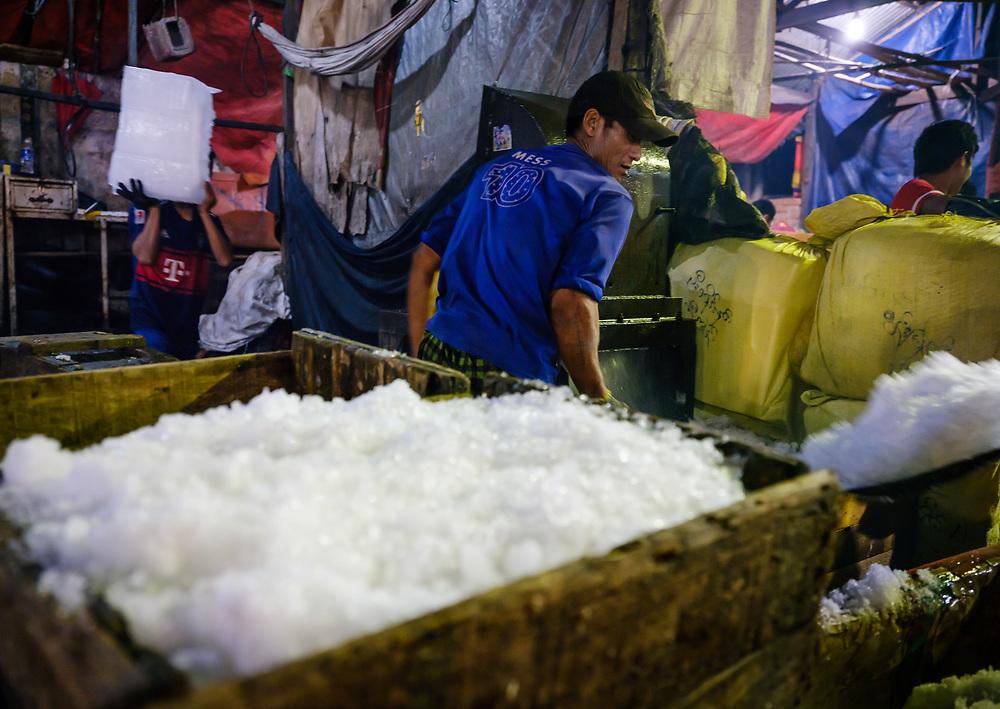 YANGON, MYANMAR - Man working with ice at the Yangon fish market.