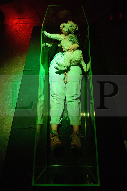 © Licensed to London News Pictures. 10/08/2017. London, UK. A visitor her dog lie in a lit neon green coffin and takes a selfie photo controlling a camera in the ceiling above them.  The artwork titled Beauty and Dead by artists Jim Townsend and Oli Cole is part of the Be Seen Dead exhibition by Made By Blah, exploring how death impacts our own identity, mortality and out complex attitudes towards it. Photo credit: Ray Tang/LNP