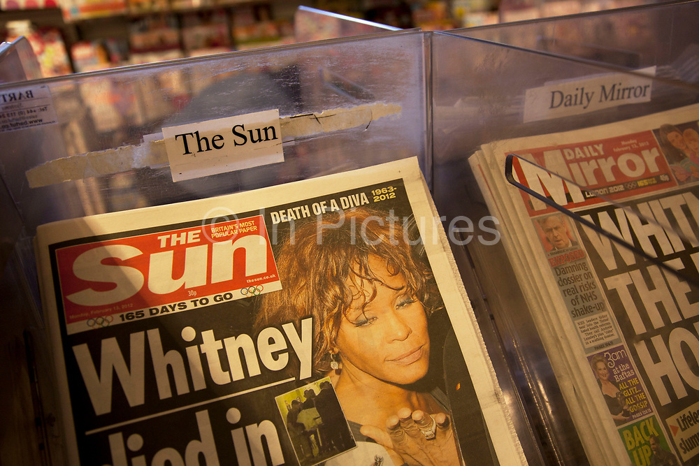 """The Sun newspaper for sale at a newsstand in London, England, UK. British police arrested five senior members of staff at News Corporation's newspaper The Sun, as part of investigations into alleged payments to police by journalists for information. This story continues the controversy surrounding News International with regards to the phone hacking scandal. Trevor Kavanagh, the newspapers's associate editor said the senior members of staff had been treated like """"an organised gang"""" and the tabloid was """"not a swamp that needed draining"""". He said money sometimes changed hands while unearthing stories, and this had always been standard practice. The Met Police declined to comment."""