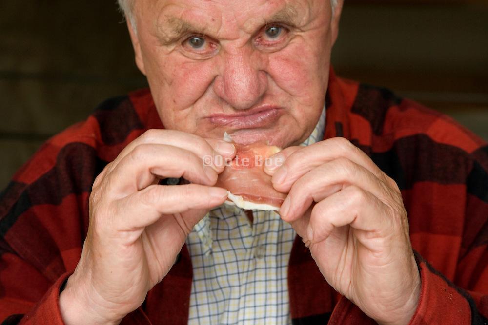 elderly man eating a bacon sandwich